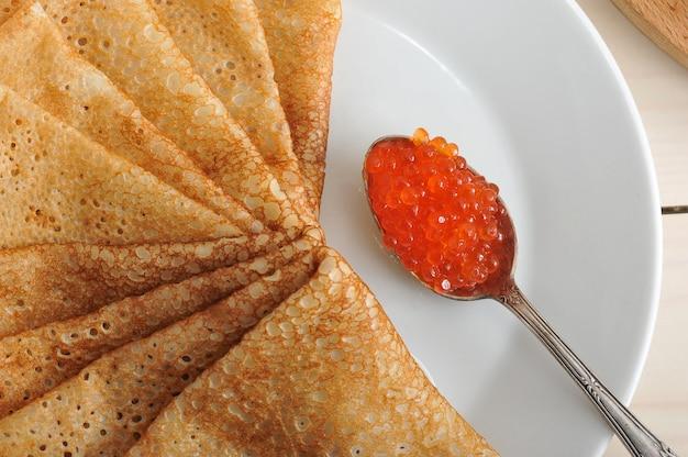 スプーンとプレートのパンケーキの赤キャビア