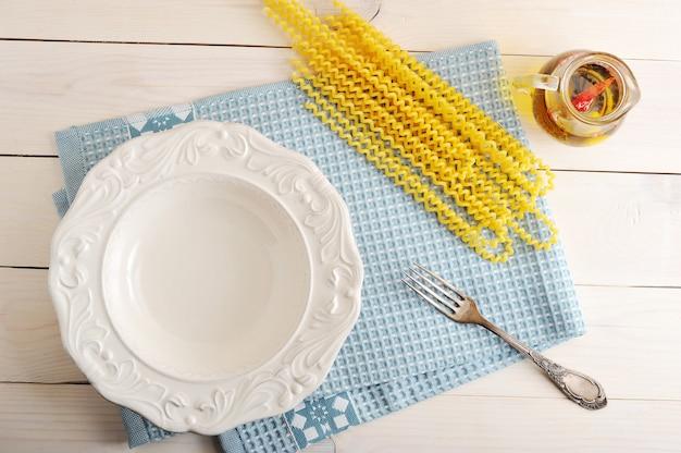 空のプレートとパスタ料理の食材
