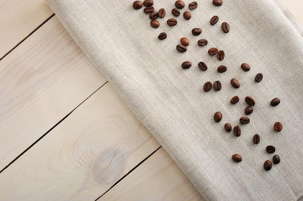 Кофейные зерна, разбросанные на льняной ткани