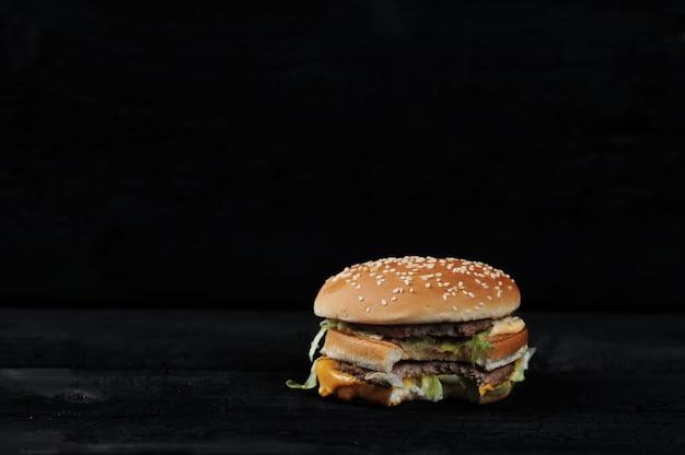暗い素朴でかまれたハンバーガー