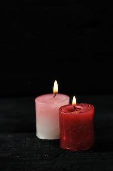 Две свечи с зажженным огнем на черном фоне