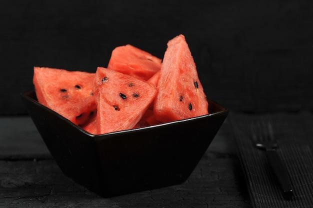 Кусочки арбуза в черной миске