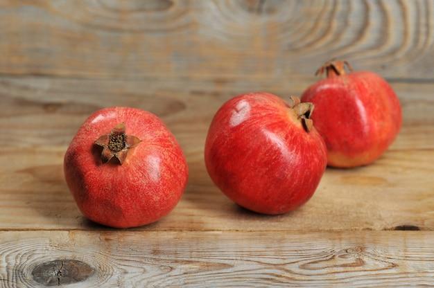 木製の背景に赤いザクロ