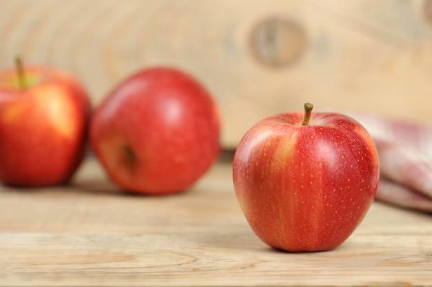 木製の背景に赤のジューシーなリンゴ
