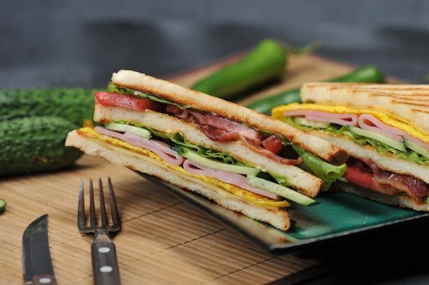 プレート上のハムとオムレツの三角形のサンドイッチ