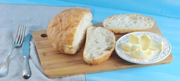 Масло на тарелку нарезанного чиабатта хлеба ножом с вилкой