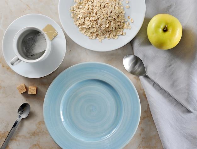 朝食のティーバッグとバター、オートミールの準備、黄色のリンゴ