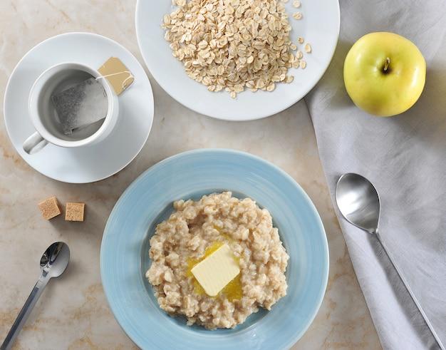 シンプルな朝食のティーバッグとバター入りのオートミール、黄色のリンゴ