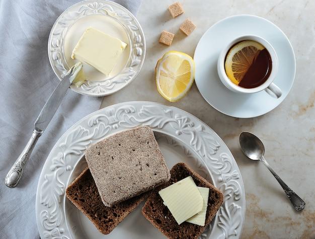 Простой завтрак чай с лимоном и ржаной хлеб с маслом