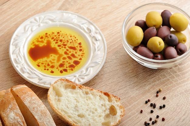 Свежий хлеб, нарезанный ломтиками с оливками и оливковым маслом с бальзамическим уксусом в миске