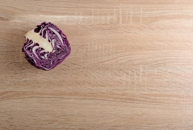 木製の背景に紫キャベツの半分の頭