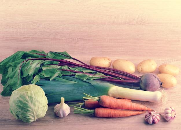 木製の背景に健康的な食事のための生野菜のセット