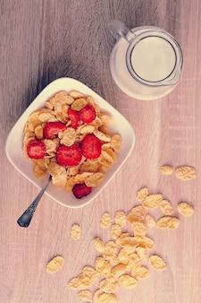 イチゴと木製の背景にミルクの水差しのコーンフレーク