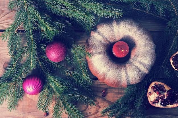 Кекс со свечой, елкой и елочными украшениями на деревянном фоне