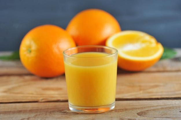 オレンジ全体の新鮮なオレンジジュースとガラス