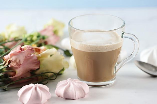 花とマシュマロと透明なマグカップのカプチーノ