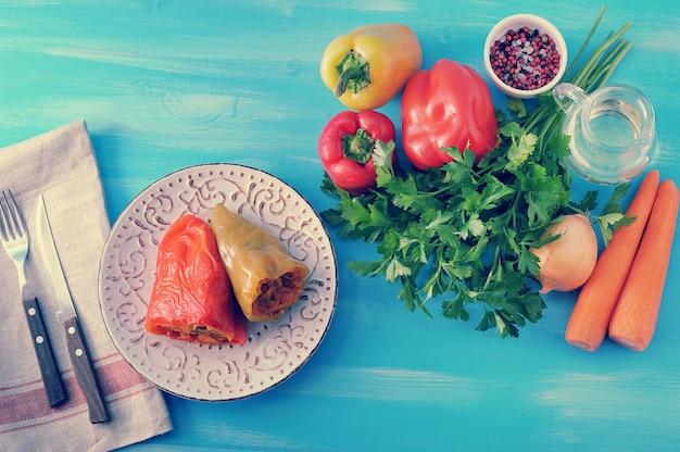 Сладкий перец, фаршированный морковью, зеленью и ингредиентами на синем деревянном фоне