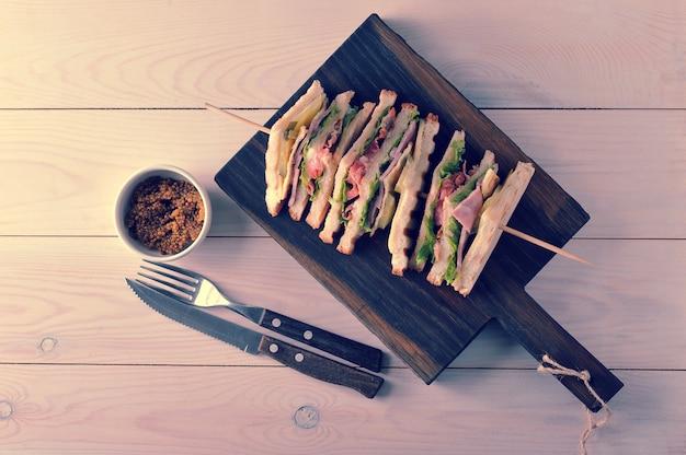 木製の串に巻きつけられたハムの三角形のサンドイッチ