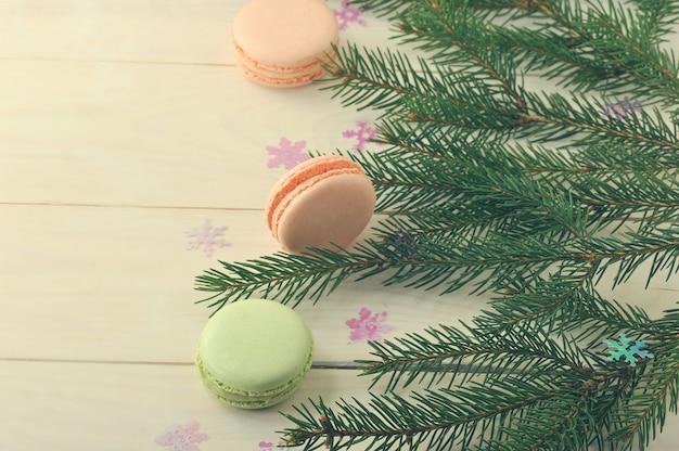 クリスマスツリーの枝と木製の背景に雪の結晶ケーキマカロン