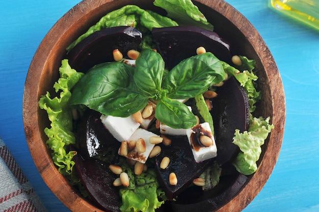 Салат из свеклы, феты, кедровых орехов в деревянной тарелке