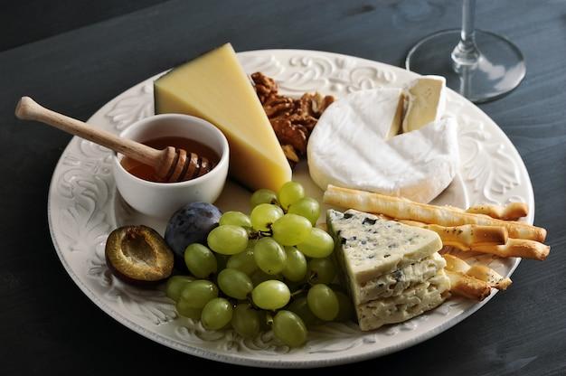 Десертный сыр, хлебные палочки, мед, орехи и виноград