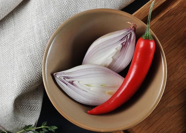 Нарезать лук и перец чили в миску