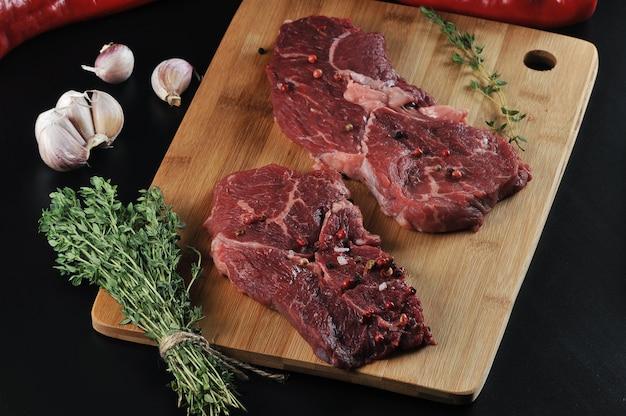 Два сырых говяжьих стейка со специями, перцем