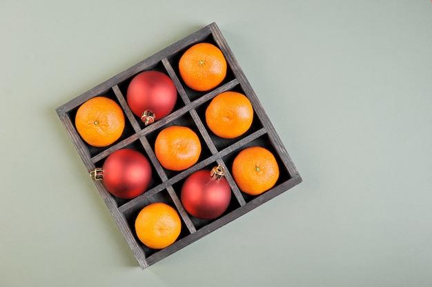 Мандарины и новогодние украшения в деревянной матричной коробке
