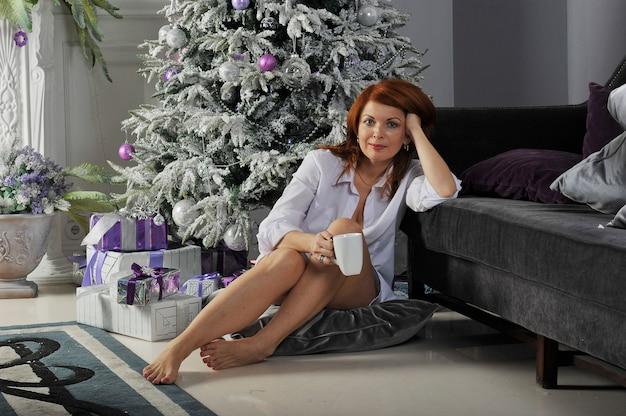 クリスマスツリーの周りの贈り物を持つ女性