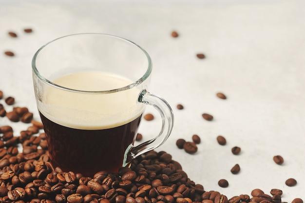 Кофе в стеклянной чашке на фоне кофейных зерен