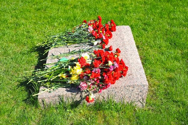 Красные гвоздики на мемориальной мраморной плите