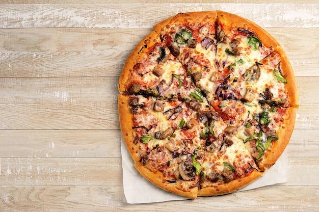丸いピザ全体を木製の背景にカット