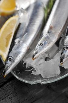 ローズマリーとレモンの魚の形のガラス皿に生のサンマ