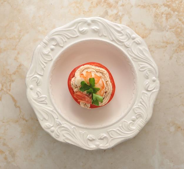 大理石の表面にエビとトマトの皿