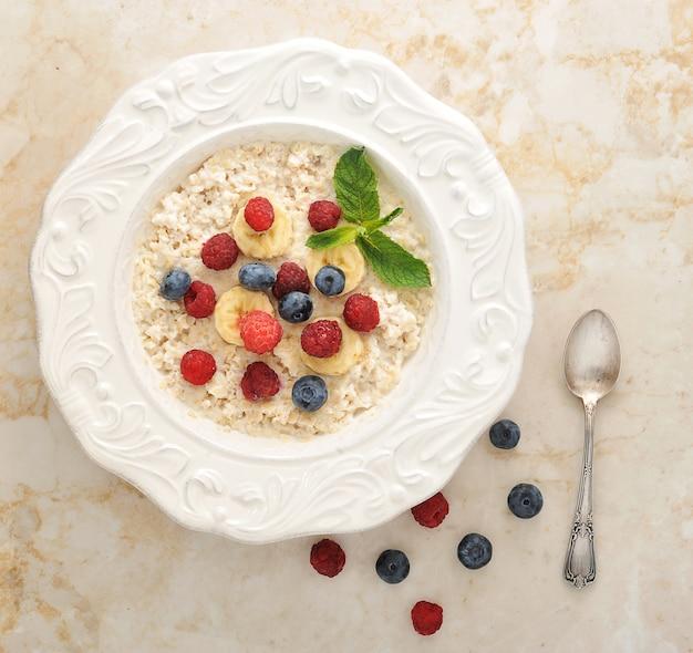 ブルーベリー、ラズベリー、バナナをボウルに入れたシリアルで健康的な朝食