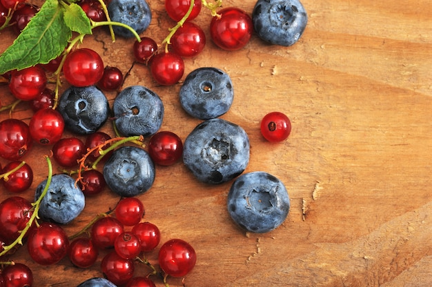 木製の表面の果実。赤スグリとブルーベリー。
