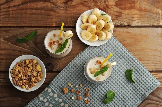 Йогурт в чашках с соломкой с мюсли и бананом