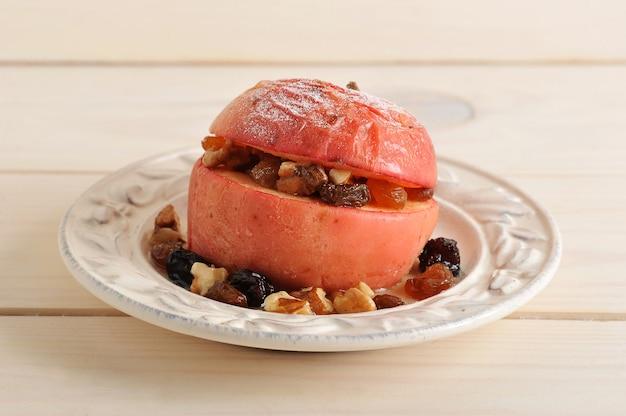 Запеченное яблоко с корицей, сахарной пудрой, изюмом и грецкими орехами в миске