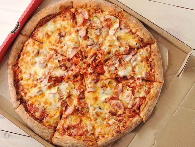 Пицца с сыром и пряными колбасками в картонной коробке