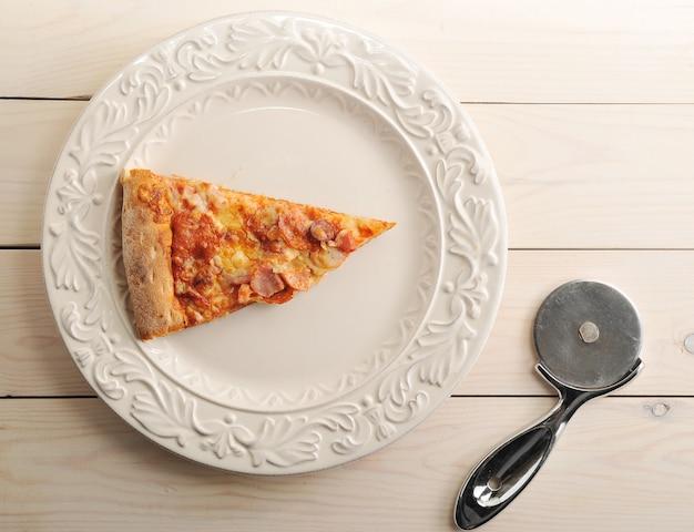 Кусочек пиццы с сыром и острыми колбасками на тарелке