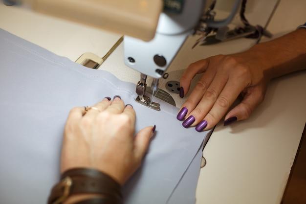 ミシンに取り組んでいる女性のテーラーの手の上からの眺め