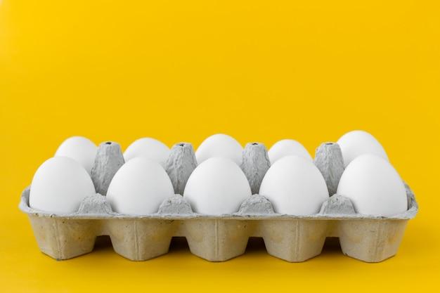 Белые куриные яйца в открытой картонной коробке на желтом фоне