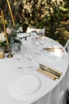 緑の自然の景色を望む屋外のゲストのための結婚式の宴会テーブル