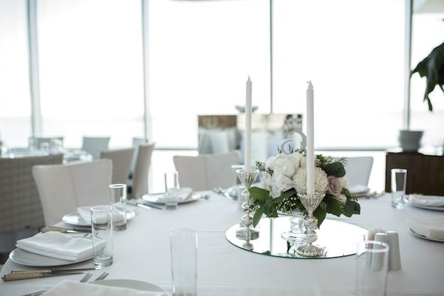 新鮮な花で飾られた結婚式の宴会テーブルの設定