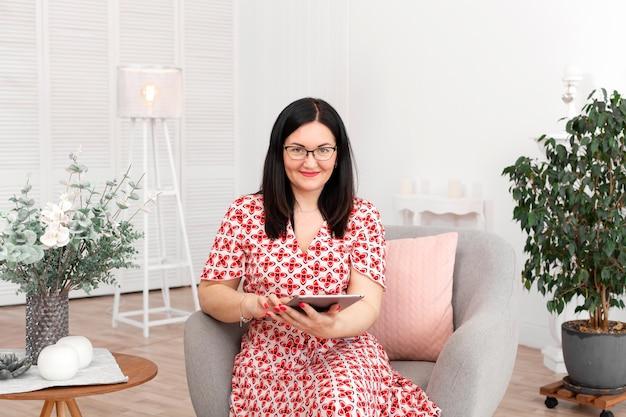 タブレットで明るいオフィスに座っている眼鏡の専門医師心理学者
