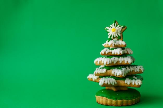 クリスマスの休日のお菓子。クリスマス休暇の伝統。緑のクリスマスツリージンジャーブレッド