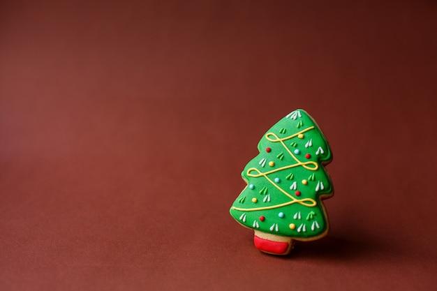 クリスマスの休日のお菓子。クリスマス休暇の伝統。濃い赤のクリスマスツリージンジャーブレッド