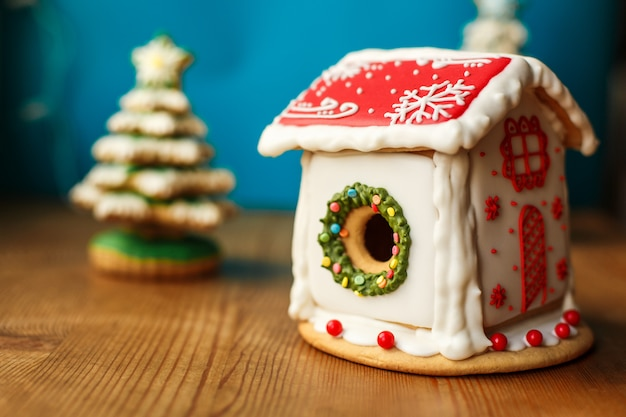 古い木製のテーブルのクリスマスジンジャーブレッドの家と休日の装飾