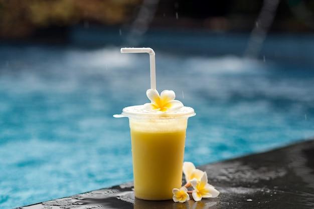 Фруктовый коктейль и цветок франжипани рядом с бассейном