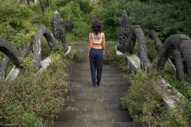 石のバリの階段上の女性